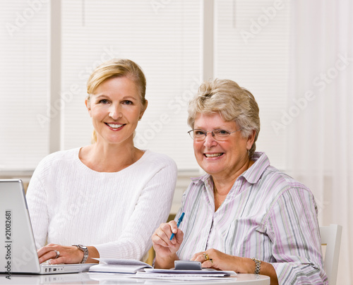 Senior woman writing checks with daughter help
