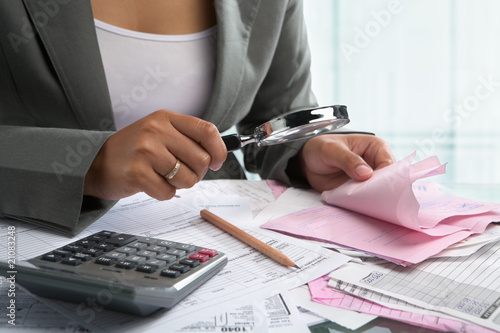 Businesswoman checking bills using magnifying glass