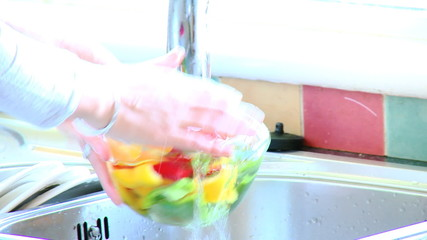 Close-up of a woman rinsing vegetables in the kitchen