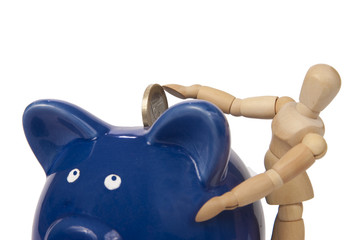 Hoelzerne Gliederpuppe steckt Euro Muenze in Sparschwein