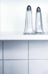 Zwei Salzstreuer auf einem Küchenregal vor weissen Fliesen