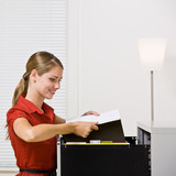 Businesswoman putting file in file cabinet