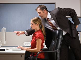 Businessman pointing at co-worker's computer