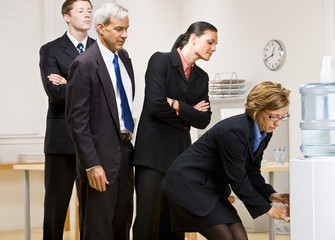 Business people waiting turn at water cooler
