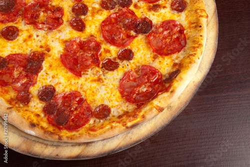 Pepperoni pizza on a wooden plate