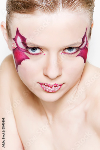 close up studio portrait of beautiful woman with bright face art