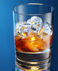Glass of brandy with ice cubes isolated on a blue