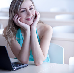 pretty young blonde woman working on a laptop computer, smiling
