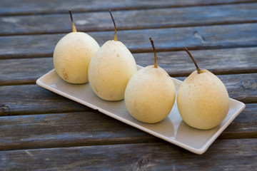 Plate of asian pears on wood table