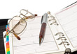 Pen and eyeglasses on agenda page