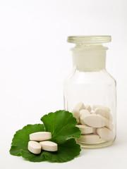 Pharmacy bottle of pills, and green leaf
