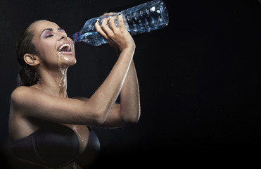 Young beauty drinking bottled mineral water