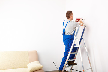 Man with drill working on ladder