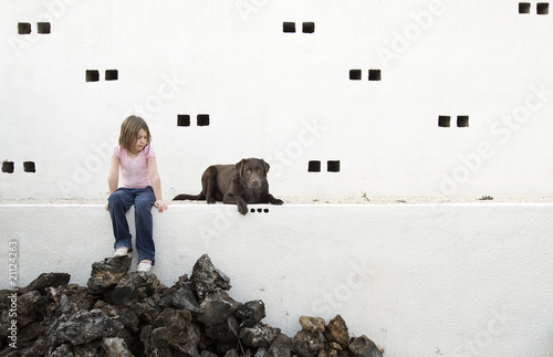 Child Sat on a Wall with her Dog