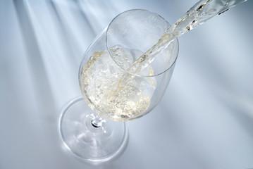 ein Glas Weisswein einschenken