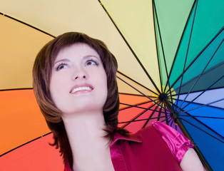 Lovely young lady standing with color umbrella