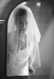Beautiful bride getting ready in front of a mirror (B&W image) poster