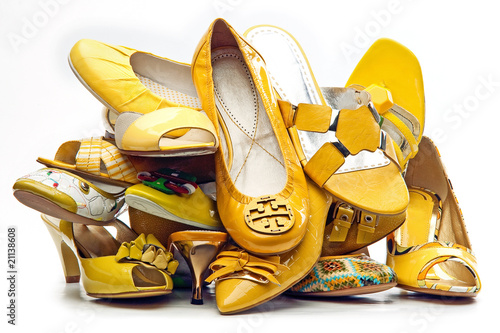 Pile of female yellow shoes isolated on white background