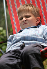 Young boy bored laying in stripped sunbed outdoor