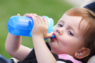 Baby girl child drinking from blue plastic bobtle