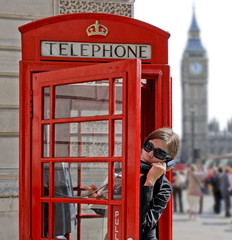 Tourist in a typical red telephone box in London