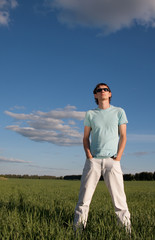 Man in sunglasses looks up in the sky