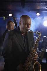 Saxophonist and Double Bass Player Performing in Jazz Club