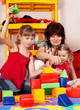 Children  with  block and senior woman in play room.