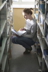 Young woman crouches at library shelf with laptop