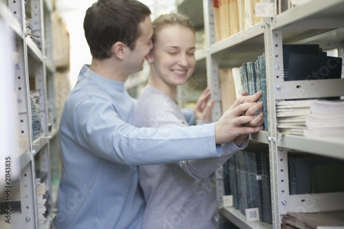 Young couple and library shelf
