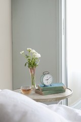 Bedside table with cut flower and alarm clock