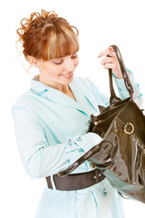 Smiling young woman searches for something in handbag