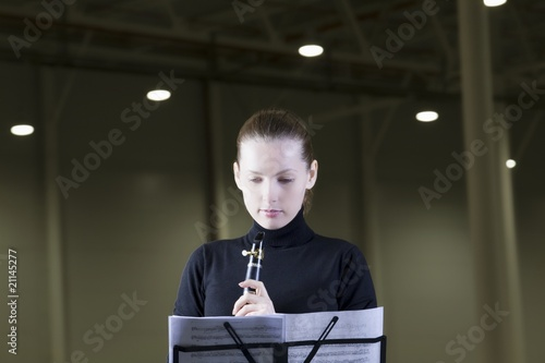 Clarinet player stands with sheet music under spotlights