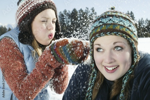 Teenage girl blows snow on her friend