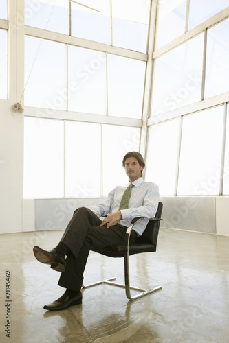 Businessman sits in  sunlit office with knees crossed