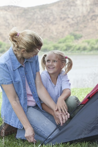 Mother and daughter pitch a tent