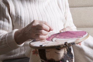 Elderly woman sits working on needlepoint