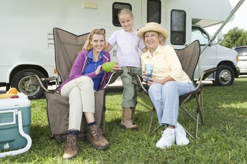 Mother, daughter and grand daughter sit outside RV home