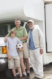 Father, son and grandson stand with RV home
