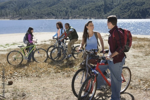 Group of fiends stand at lakeside with mountain bikes