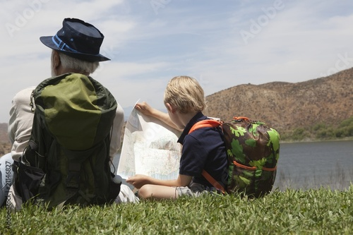 Grandfather and grandson sit with map at lakeside