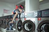 Frau im Waschsalon befüllt eine Waschmaschine