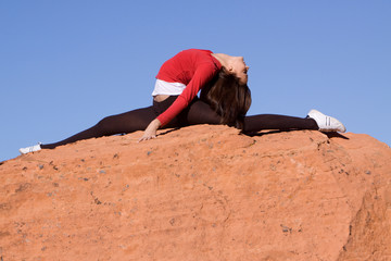 Woman doing split on the rocks
