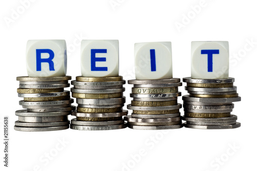 Stacks of coins with the letters REIT isolated on white