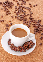 Small white cup of coffee with coffee grain on brown background