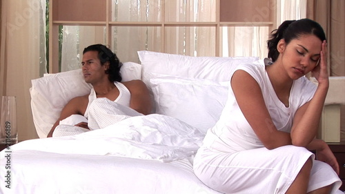 Distressed couple having an argument sitting on bed