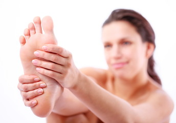 Young woman massages her foot