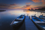 Fototapety Peaceful sunrise with dramatic sky and boats and a jetty