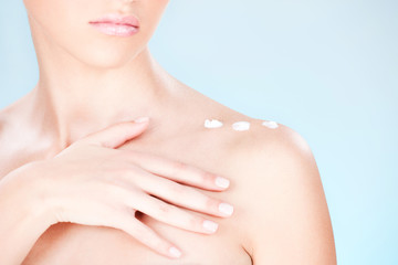 cosmetic cream on woman's shoulder