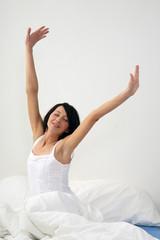 junge Frau sitzt im Bett und dehnt sich
